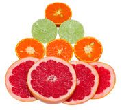 Sections of citrus fruits. Sections of ripe juicy grapefruit, tangerine and lime on white background. Focus on grapefruit. Isolated Stock Photos