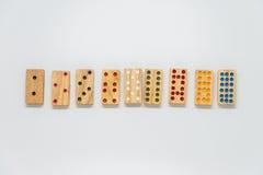 Secuencia de dominós de madera en el fondo blanco con el foco selectivo Imagenes de archivo