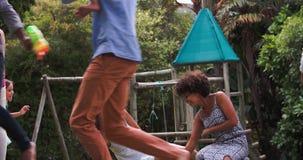 Secuencia de la cámara lenta de familias que juegan en jardín junto metrajes