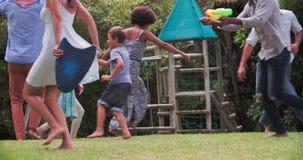 Secuencia de la cámara lenta de familias que juegan en jardín junto almacen de video
