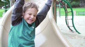 Secuencia de la cámara lenta de muchacho que juega en diapositiva en patio metrajes