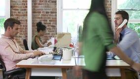 Secuencia del lapso de tiempo de trabajadores en los escritorios en oficina conceptora almacen de video