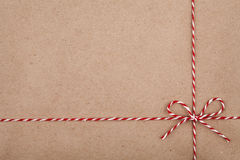 Secuencia o guita de la Navidad atada en un arco en el contexto del papel de Kraft Fotos de archivo