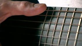 Secuencias conmovedoras de la guitarra de la mano del hombre Funcionamiento de la música Vídeo estupendo de la macro de la cámara almacen de video