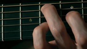 Secuencias conmovedoras de la mano del guitarrista en fretboard Funcionamiento de la música vídeo de la macro 4K metrajes