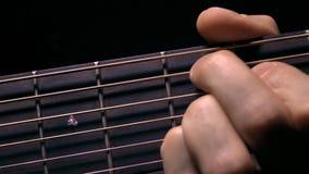 Secuencias conmovedoras de la mano masculina en fretboard Funcionamiento de la música vídeo de la macro 4K almacen de metraje de vídeo