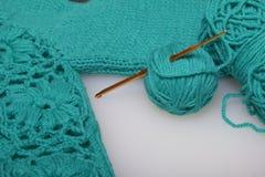 Secuencias del hilo para hacer punto color esmeralda y los ganchos para hacer punto Mentira en un producto hecho punto listo Fotografía de archivo libre de regalías