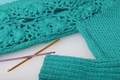 Secuencias del hilo para hacer punto color esmeralda y los ganchos para hacer punto Mentira en un producto hecho punto listo Foto de archivo libre de regalías