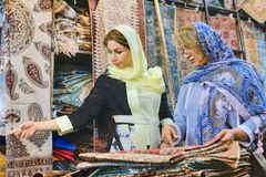 Secular Iranian women choose goods for purchase in carpet store. Fars Province, Shiraz, Iran - 19 april, 2017: Two fashionable Iranian women, young and mature Royalty Free Stock Photography