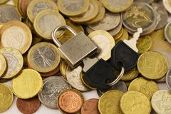 Secure cash savings or investments concept with padlock and key on various coins stock image