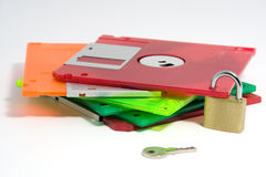 Secure Data. A pile of coloured floppy discs, secured with a padlock. Isolated on a white background Stock Image