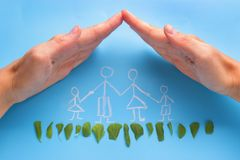 Secure family concept. Family protected by hands royalty free stock photo