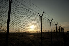 Secure fence. At sunset with sun behind it royalty free stock photos
