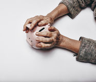 Secure investments. Top view of senior woman hands holding a piggy bank on grey surface. Elderly hands grabbing a small piggybank. Concept of secure investments stock photos