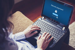 Secure payment on the screen. Woman typing on a laptop. Stock Image