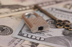 Secure payments. Padlock and bronze key on dollar bills Royalty Free Stock Photos