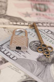 Secure payments. Padlock and bronze key on dollar bills. Deep of field photo Stock Photography
