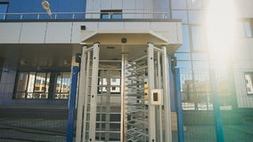 Secure turnstile at the entrance to the territory of the modern factory. Camera pulls back from the turnstile and the