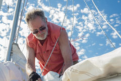 Securing the Sail. A man secures the sail to the mast of his sailboat under a blue sky dotted with clusters of clouds stock photos