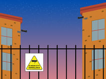 Security. Night falls onto buildings protected by fencing and security cameras Stock Photography