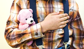 Security. Concept. The boy is holding small teddy bear in his arms. In vintage style royalty free stock image