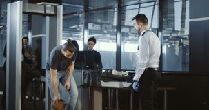 Security agent patting down a male passenger. Security agent at an airport check-in gate patting down a bearded casual male passenger with outstretched arms stock video