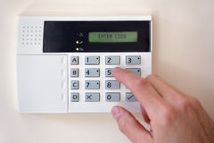 Home security. Security alarm keypad with person arming the system Stock Photography