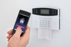 Security alarm keypad with person disarming the system Royalty Free Stock Photography