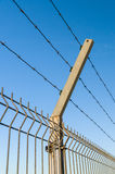 Security barbed wire fence against blue sky Stock Photography