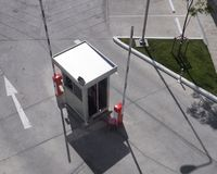 Security booth with open barriers. Aerial view of security booth with open barriers at a parking lot stock image