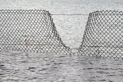 Security Breach - Water Fence. Open part in a fence in the water... Security Breach concept... Focus on the fence with the water blurred Royalty Free Stock Images