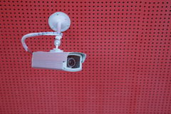 Security camera. A security camera is on a red ceiling Stock Photo