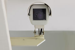 Security Camera. A security camera looks down directly at you from the corner of a building Stock Photography