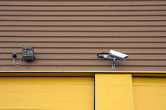 Security camera. A security camera and a spot light on a warehouse Royalty Free Stock Image