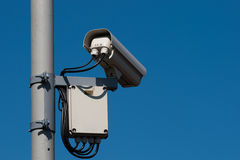Security Camera. Security / surveillance camera against a clear blue sky stock images