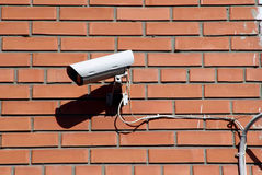 Security camera. On a red brick wall Stock Images