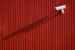 Security camera. Outdoor white security camera with shadow on the red wall royalty free stock photography