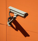 Security camera. On a orange wall royalty free stock image