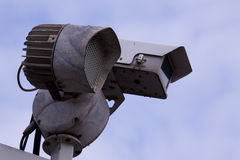 Security camera. Video security camera on a post against the sky with a dedicated light Royalty Free Stock Photo