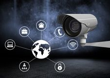 Security camera against dark background with world business icons. Digital composite of Security camera against dark background with world business icons stock image