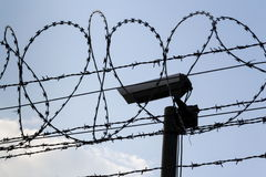 Security camera behind barbed wire fence around prison walls Royalty Free Stock Photo