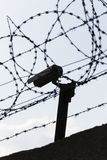 Security camera behind barbed wire fence around prison walls Stock Photography