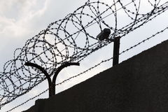 Security camera behind barbed wire fence around prison walls Stock Image