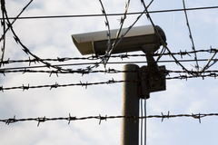Security camera behind barbed wire fence around prison walls Royalty Free Stock Photos