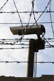 Security camera behind barbed wire fence around prison walls Stock Photos