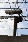 Security camera behind barbed wire fence around prison walls Stock Photo