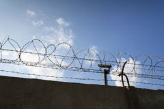 Security camera behind barbed wire fence around prison walls Royalty Free Stock Images