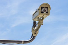Security camera with blue sky background. Grey security camera with blue sky background Stock Photography