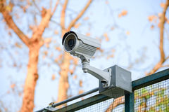 Security Camera CCTV over fence blue sky Royalty Free Stock Photo