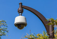 Security camera, CCTV in the park. Security camera, CCTV hangs in park for monitoring with the blue sky background Royalty Free Stock Images